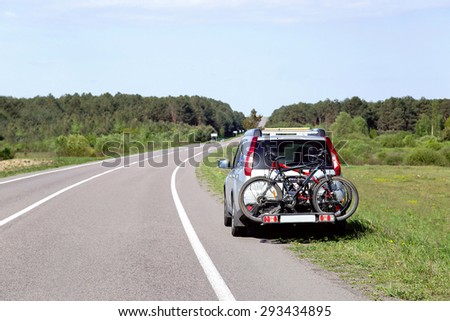 Let's go on a trip! The car is by the road and ready to travel. Two bicycles mounted on trunk of jeep. Empty place for message. Copy space. Vacation, freedom, adventure, transportation concept.  - stock photo