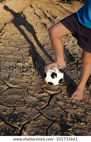 Let's play football! Boy with ball on village road, on the dry ground. - stock photo