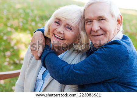 Let the love last forever. Happy senior couple bonding to each other and smiling while sitting on the park bench together  - stock photo