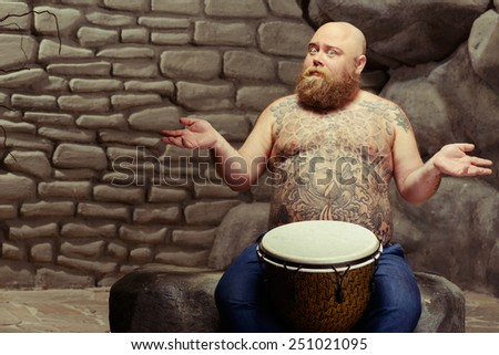 Let the music move you. Portrait of funny bearded shirtless man with tattooed body sitting with the drum and spreading his hands while sitting against stonewall background - stock photo