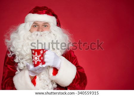 Let us have a little tea break. Cheerful Father Christmas holding a cup of warm tea looking excited to the camera