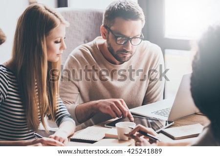 Let us look at our statistics! Young handsome man pointing at digital tablet while sitting at the office table on business meeting with his coworkers - stock photo