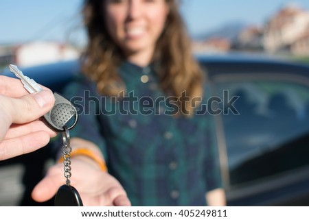 Let you be the driver. Young female being handed the car keys - stock photo
