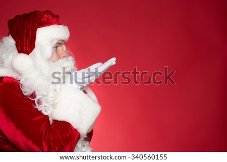 Let your wishes come true. Closeup profile of Santa blowing something off his hands towards copyspace on the side on red background - stock photo