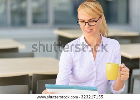 Lets catch the latest news. Cheerful attractive businesswoman drinking tea and holding newspaper while reading - stock photo