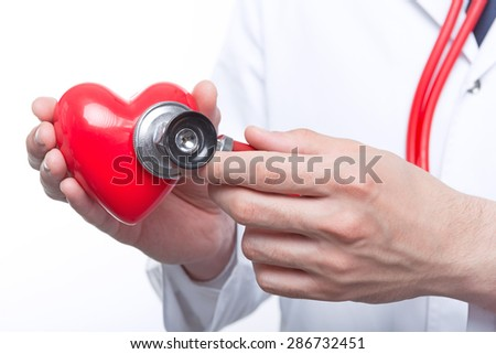 Lets check. Close up of male doctor hands holding the heart and keeping stethoscope on it.