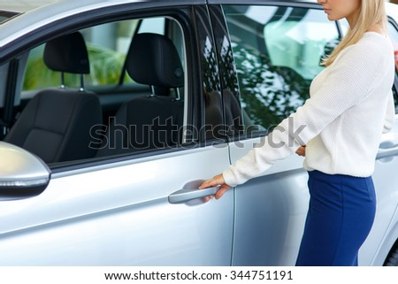 Lets drive. Close up of nice modern woman opening the car while going to test it in auto show - stock photo