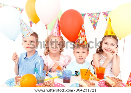 Lets fly. Group of little cheerful kids sitting at table during birthday party and holding colorful balloons.