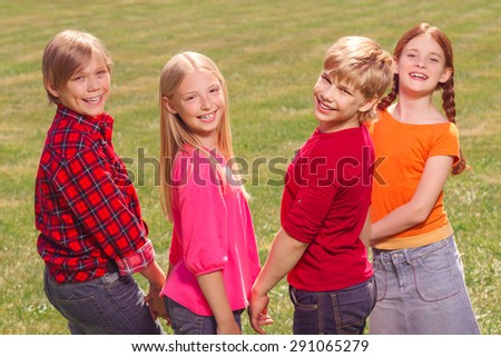 Lets have fun. Little nice children standing in raw and smiling while having fun in the yard. - stock photo