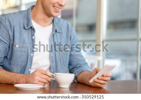 Lets make a call.  Close up of pleasant smiling handsome man holding mobile phone and going to phone while drinking coffee in the cafe - stock photo