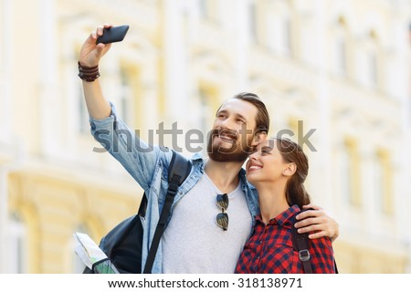 Lets make photo. Blissful young nice tourist holding mobile phone and bonding to each other while making selfie - stock photo