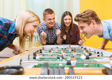 Lets play. Beautiful young blond girl looking smiling at her partner while playing air hockey wearing checkered shirt in a yellow room, while friends cheering them up - stock photo