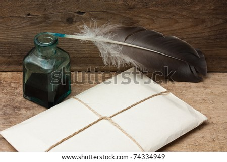 letter and quill pen with ink on a wooden background - stock photo