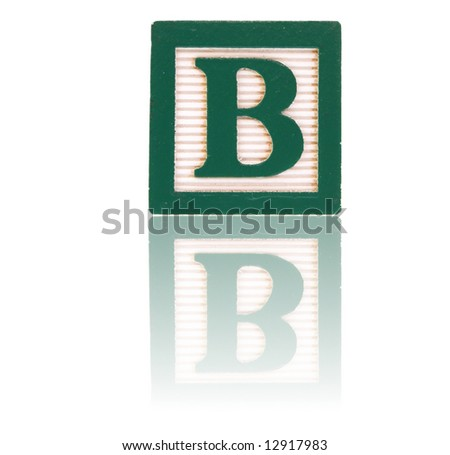 letter b in an alphabet wood block on a reflective surface - stock photo