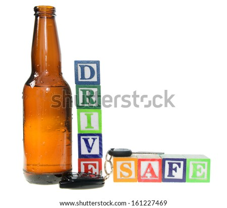 Letter blocks spelling drive safe with a beer bottle and keys. Isolated on a white background - stock photo