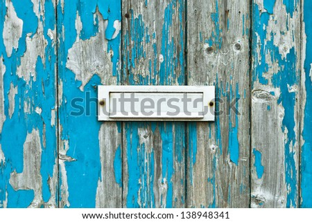 Letter box in a weathered wooden door - stock photo