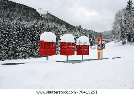 Letter boxes are covered with snow beside an SOS phone device in a remote mountain village - stock photo