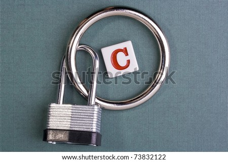 """Letter """"C"""" in the middle of a metal circle attached to a lock. - stock photo"""