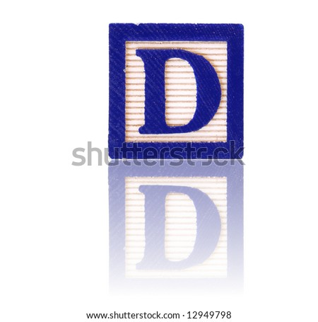 letter d in an alphabet wood block on a reflective surface - stock photo