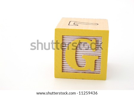 letter g in a alphabet wood block on a white surface - stock photo