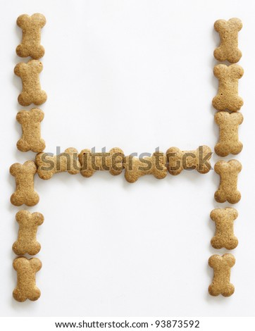 Letter H made of bone shape dog food on white background, shot directly from above