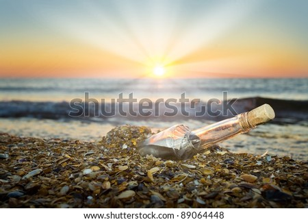 letter in a bottle on the beach at sunset - stock photo