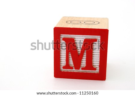 letter m in an alphabet wood block on a white surface - stock photo