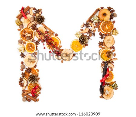 """Letter """"M"""" made of Christmas spices, dry orange and apple slices and small gifts. Isolated on white background - stock photo"""