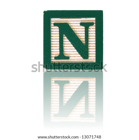 letter n in an alphabet wood block on a reflective surface - stock photo