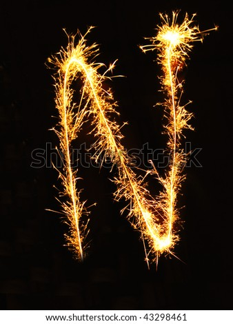 Letter N made of sparklers isolated on black - stock photo