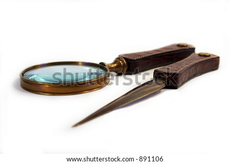 Letter opener and magnifying glass on white background