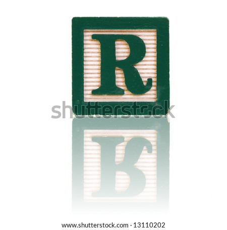 letter r in an alphabet wood block on a reflective surface - stock photo