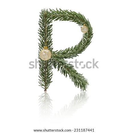 Letter R made from fir branches, decorated with christmas balls and reflection. - stock photo