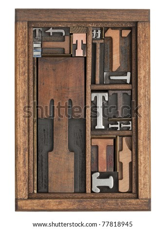 letter T abstract - vintage letterpress printing blocks of different size and style in a wooden box with dividers - stock photo