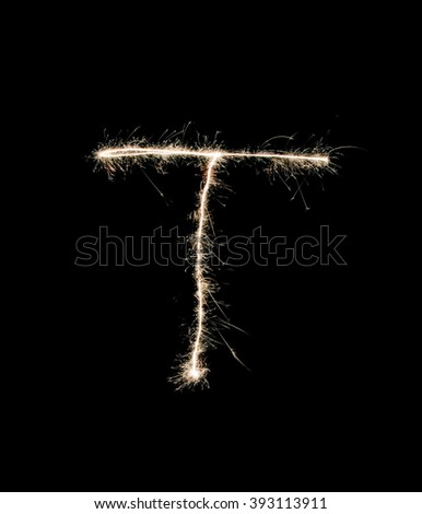 Letter T drew with spakrs on a black background. - stock photo