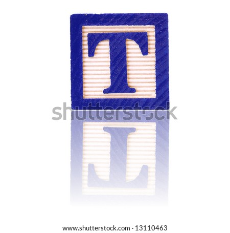 letter t in an alphabet wood block on a reflective surface - stock photo