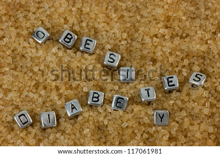 Letter tiles spelling out the words Obesity and Diabetes on a background of brown sugar - stock photo