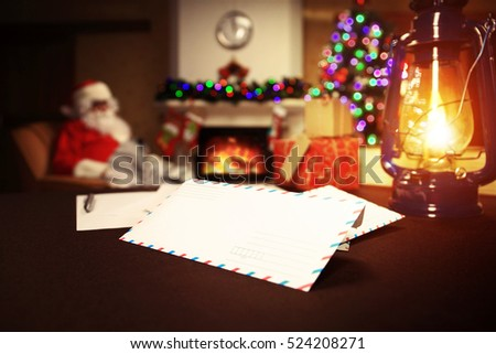 Letter to Santa Claus near the gift and candles. Home decoration.