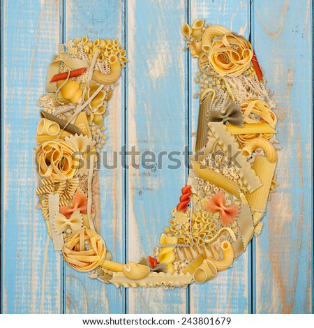 Letter U made from pasta on a blue wooden  background  - stock photo