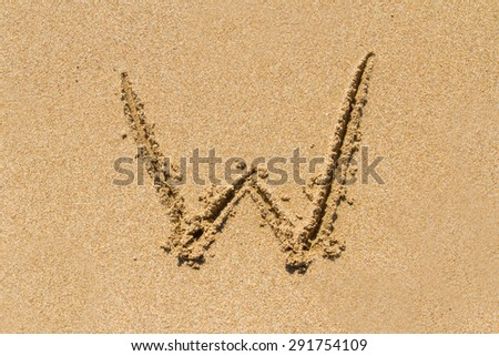 Letter W of the alphabet written on sand with upper case. - stock photo