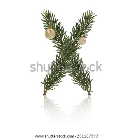 Letter X made from fir branches, decorated with christmas balls and reflection. - stock photo