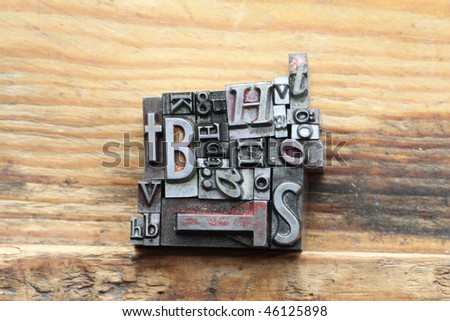 letterpress type on a wooden background with random letters. - stock photo