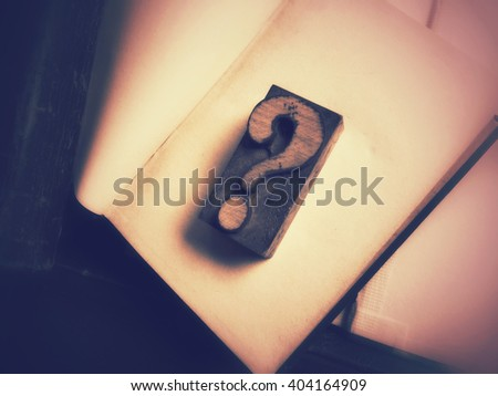 Letterpress wood type question mark on blank pages of old book - stock photo