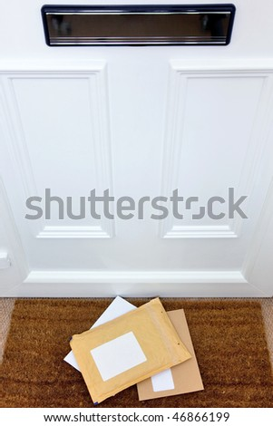 Letters and a package lying on a doormat, blank labels to add your own name and address, focus on the letters. - stock photo