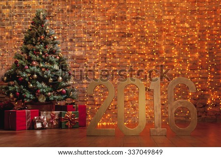 Letters 2016 and decorated Christmas tree on brick wall background - stock photo