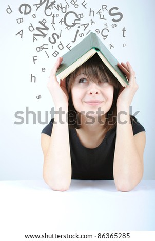 Letters falling from top on student girl with book - stock photo