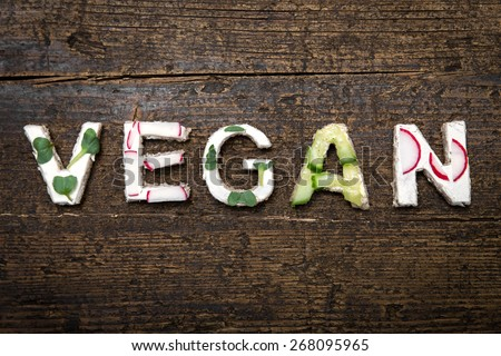 letters of healthy vegetable canapes builds the word Vegan on a old wooden table