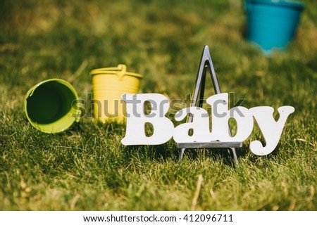 letters of word baby and knitted socks hanging on clothesline  - stock photo