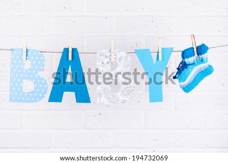 letters of word baby and knitted socks hanging on clothesline against white brick wall - stock photo