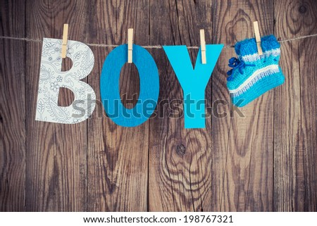 letters of word boy and knitted socks hanging on clothesline against wooden background - stock photo
